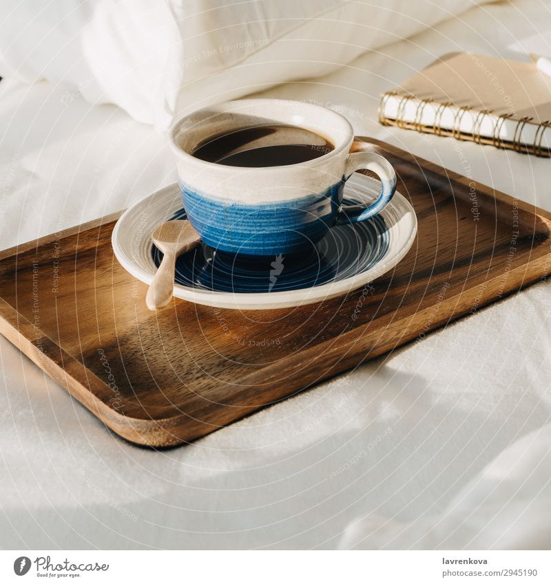Coffee on wooden tray with notebook and pen on bed Neutral Background Bedroom Beverage Breakfast Brown Cup Hot Morning Mug Notebook Paper Pen Pillow Sheet Spoon