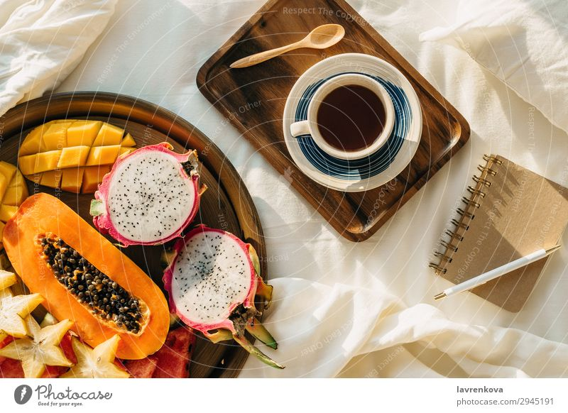 Coffee or tea on wooden tray and tropical fruit plate Tropical Exotic Carambole Mango pitahaya Dragonfruit Plate Healthy Eating plant based Vegan diet Papaya