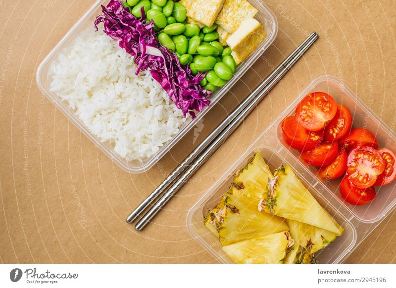 Healthy asian-style vegan bento box flat lay cherry tomatoes Cut Pineapple Red cabbage Tasty Green Cooking metal chopsticks take away lunch box zero waste