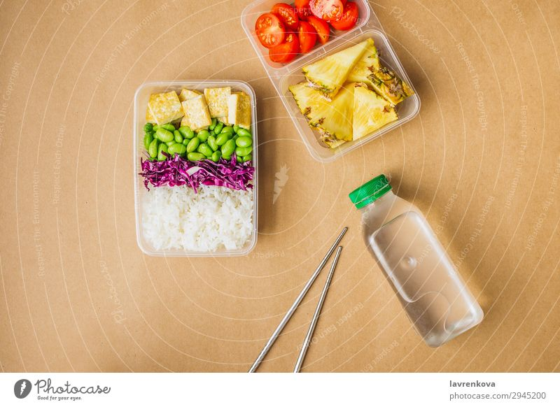Healthy asian-style vegan bento box Green Bottle Water flat lay cherry tomatoes Cut Pineapple Red cabbage Tasty Cooking metal chopsticks take away lunch box