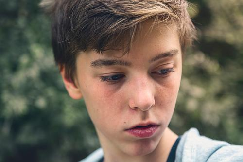Portrait of a young man looking down, lost in thought pensive portrait teenager serious thoughtful concentration boy male beautiful casual caucasian outdoor