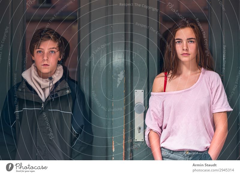 portrait of a boy and girl in front of a green door teen teenager teens two person confident street outdoor entrance casual young woman male caucasian female