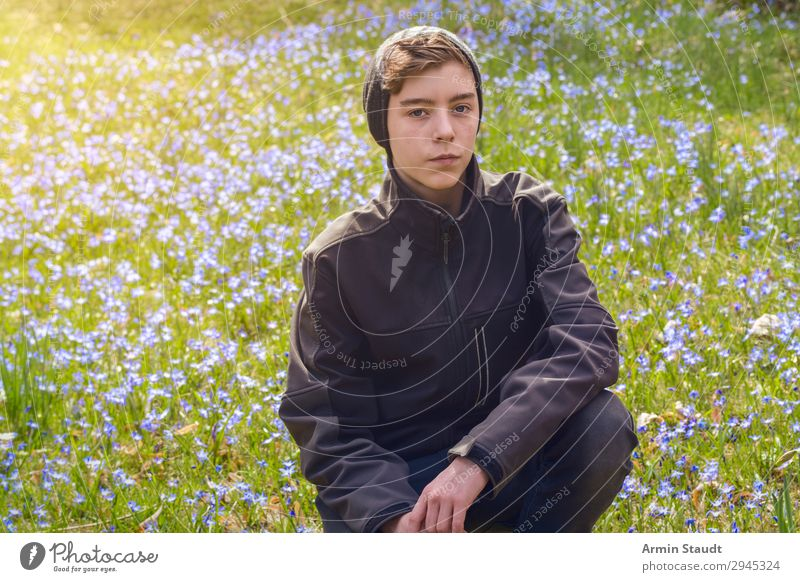 portrait of a boy crouching on a spring meadow with many flowers male young outdoor sunlight blue nature grass green park caucasian cap serious teenager looking