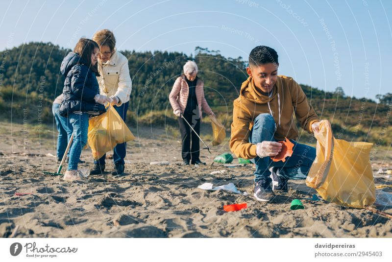 Young man cleaning the beach Human being Man Hand Beach Adults Environment Family & Relations Group Work and employment Sand Dirty Plastic Trash Teamwork