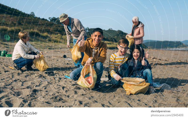 Young man and children cleaning the beach Happy Beach Child Human being Man Adults Family & Relations Youth (Young adults) Group Environment Sand Plastic