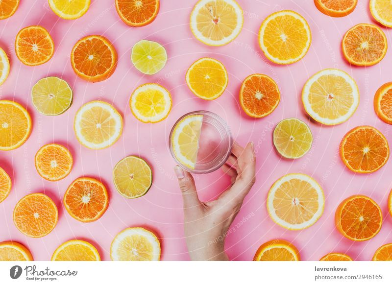 woman's hand holding lemon water with sliced citrus fruits Pink Woman flat lay sassy water Hold Hand Cut Lime Round Diet Vegetarian diet Food Healthy Eating