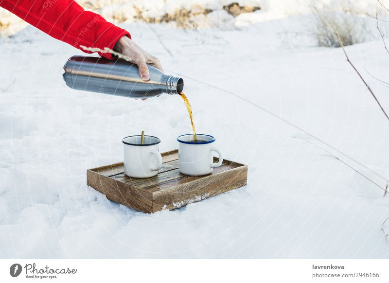 Male hand pouring hot coffee or tea into enamel cup Nature Man Hand Winter Wood Cold Snow Hiking Metal Coffee Beverage Seasons Frost Hot Frozen Box