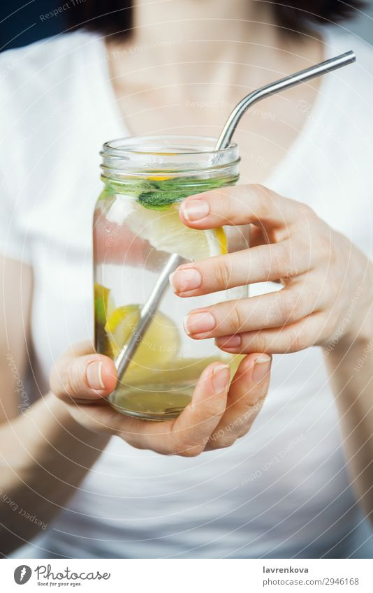 woman holding mason jar with sassy lemon and mint water Straw Metal Lemon Citrus fruits focus Selective Breakfast Beverage Drinking Mint Lime Water