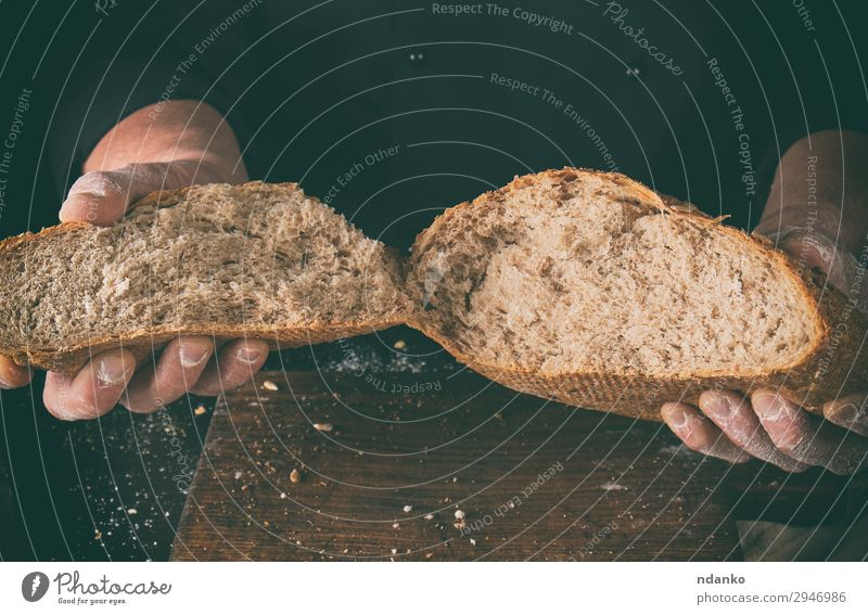 broken off crusty bread baked from rye flour Bread Nutrition Table Kitchen Cook Human being Hand Fingers Wood Make Dark Fresh Brown Black White Tradition grain