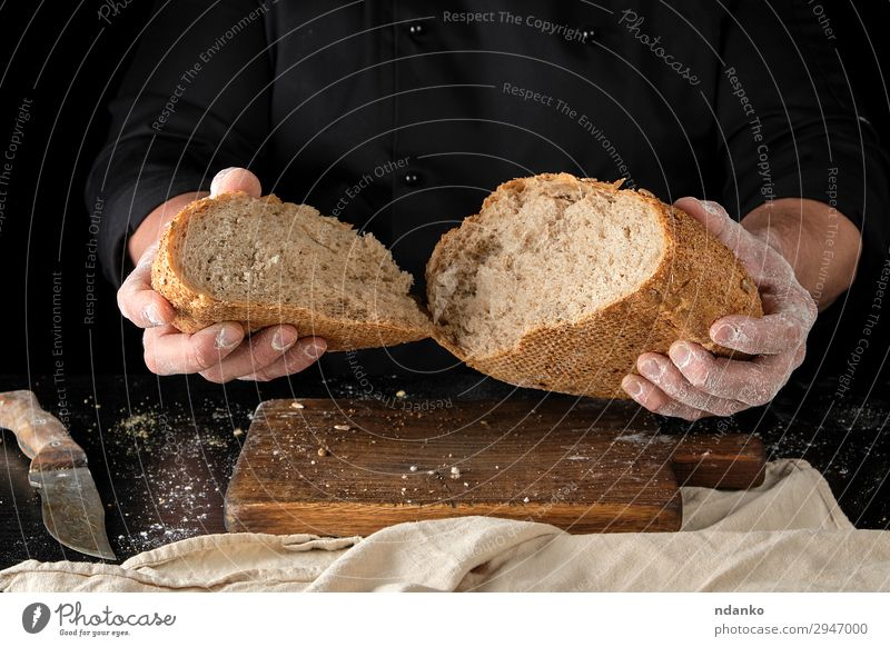 chef holds broken in half round rye bread Bread Nutrition Knives Table Kitchen Human being Hand Fingers Wood Make Dark Fresh Hot Brown Black White Tradition Rye