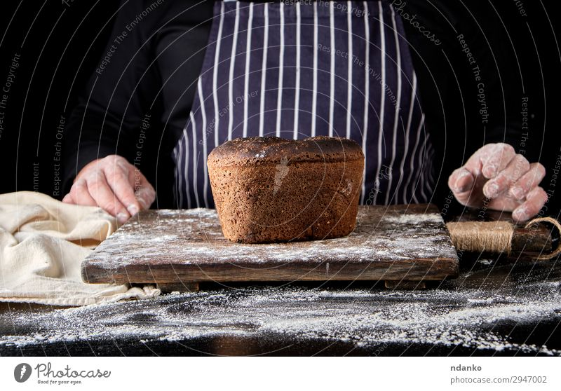 baked rye bread on a brown wooden board Bread Nutrition Eating Lunch Dinner Diet Table Kitchen Cook Man Adults Hand Wood Make Dark Fresh Delicious Natural Brown