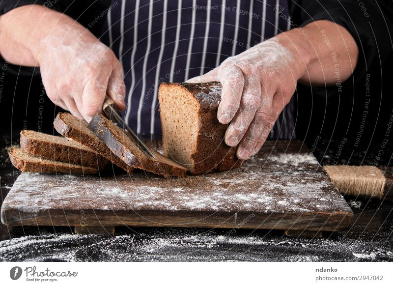 chef in black uniform holds a kitchen knife Bread Nutrition Eating Lunch Dinner Knives Table Kitchen Man Adults Hand Wood Dark Fresh Delicious Natural Brown
