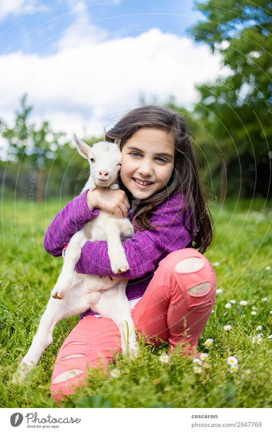 Little girl hugging a goat on a field Woman Child Human being Sky Vacation & Travel Nature Summer Plant Beautiful Green White Flower Relaxation Animal Joy Girl