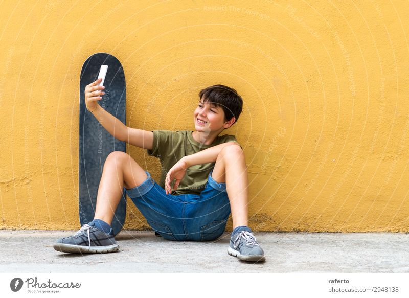 boy sitting on ground leaning on a wall, taking a selfie Happy Child Telephone PDA Technology Human being Boy (child) Youth (Young adults) 1 13 - 18 years