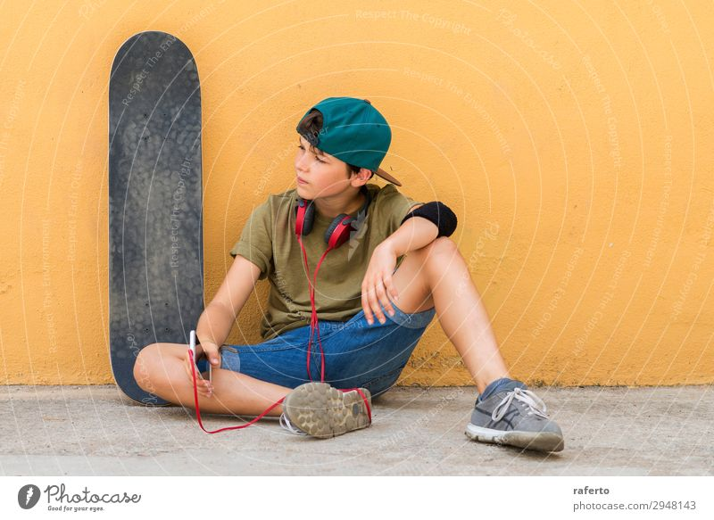 boy sitting on ground leaning on a wall while using a mobile Child Telephone PDA Technology Human being Masculine Boy (child) Youth (Young adults) 1