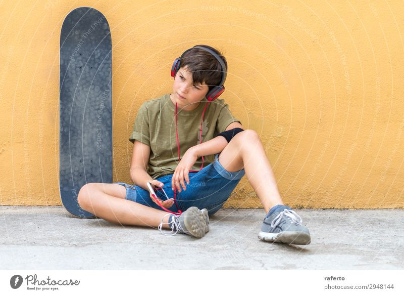 boy sitting against a yellow wall, listening music by headphones Lifestyle Style Happy Beautiful Leisure and hobbies Freedom Music Telephone Headset PDA