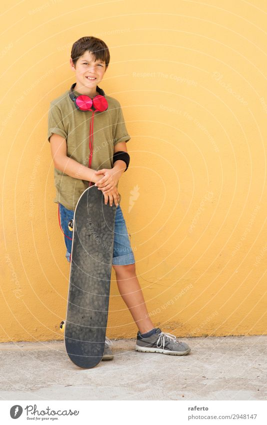 Young boy leaning on a yellow wall with headphones on neck Style Music Child Telephone PDA Human being Masculine Boy (child) Young man Youth (Young adults) Man