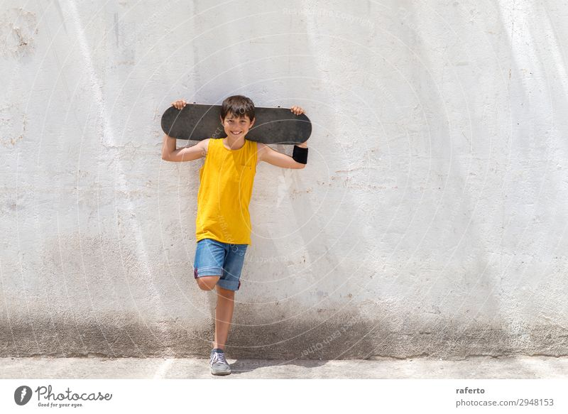 Young smiling boy leaning on yellow wall holding a skateboard Style Happy Child Human being Masculine Boy (child) Young man Youth (Young adults) 1