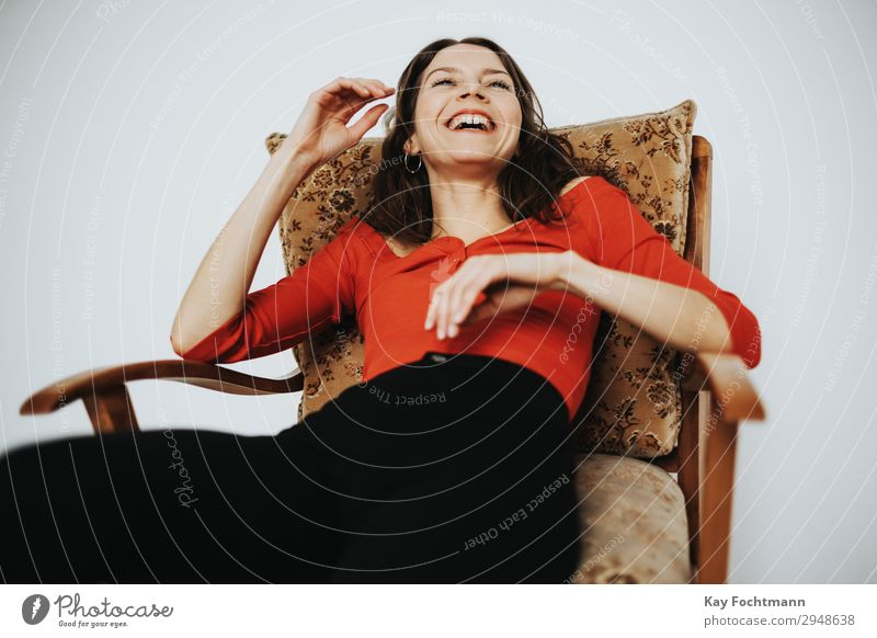 Woman sitting in armchair laughing Lifestyle Contentment Living or residing Flat (apartment) Armchair Feminine Young woman Youth (Young adults) Adults