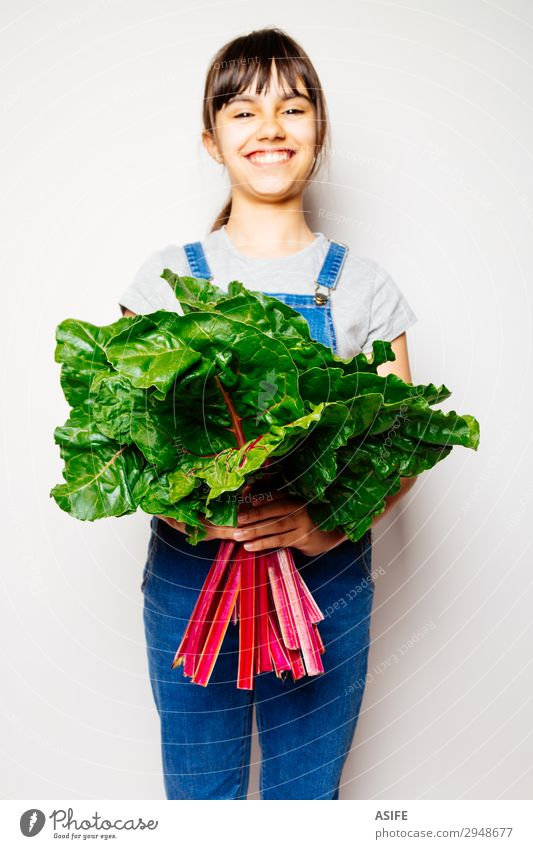 Happy girl holding a bunch of swiss chard Vegetable Nutrition Vegetarian diet Diet Joy Child Leaf Smiling Fresh Natural Green Red White rainbow chard Vegan diet
