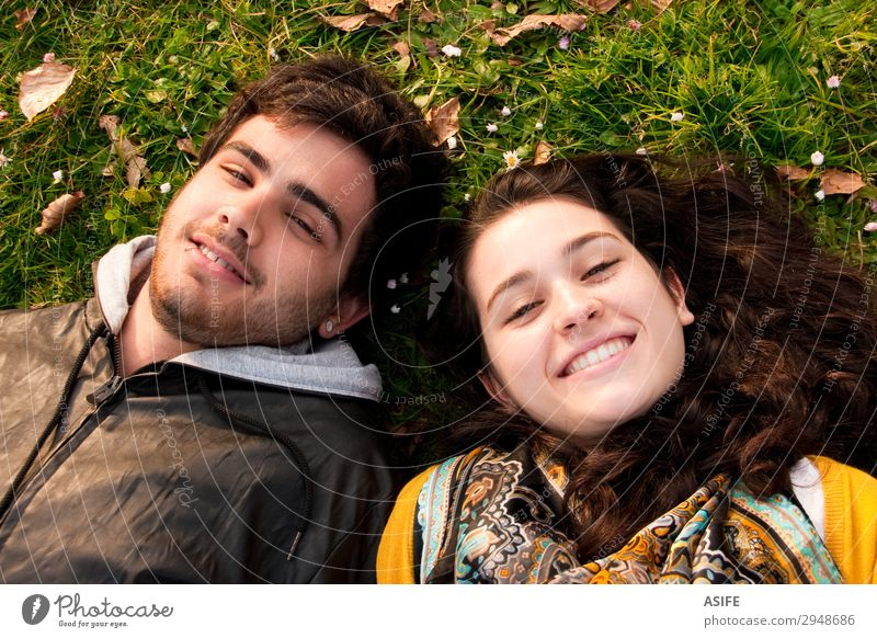a couple of teenagers lying in the grass Lifestyle Joy Happy Beautiful Relaxation Leisure and hobbies Human being Woman Adults Man Sister Friendship Couple