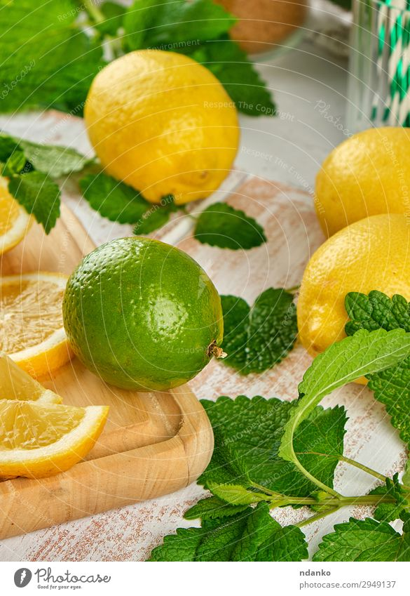 ripe yellow lemons and lime, mint green Fruit Cold drink Lemonade Juice Table Leaf Wood Fresh Above Juicy Brown Yellow Green White bunch citrus Cocktail food