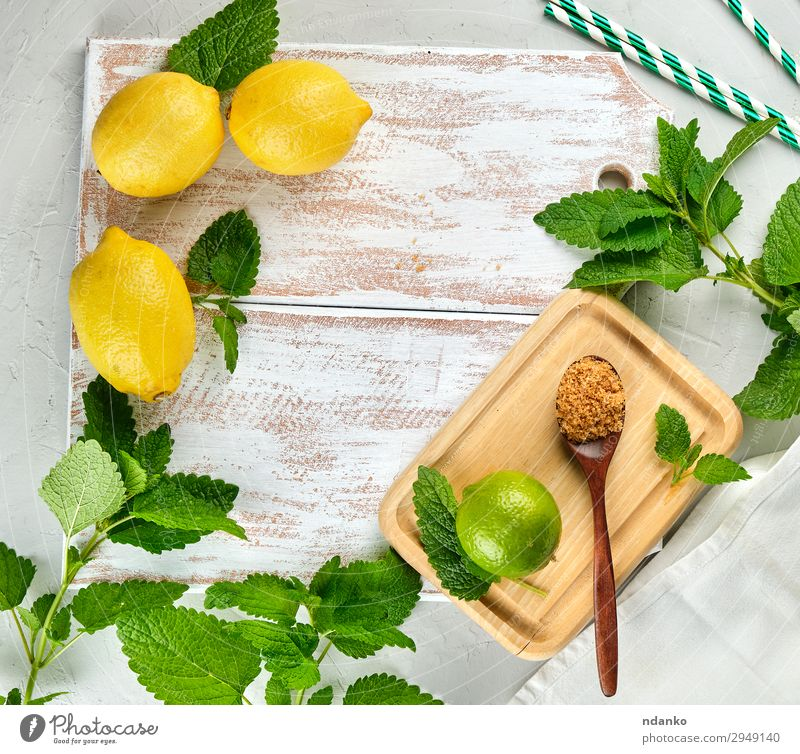 whole lemons and lime, brown sugar Fruit Herbs and spices Lemonade Juice Spoon Table Leaf Tube Wood Fresh Above Juicy Brown Yellow Green White bunch citrus