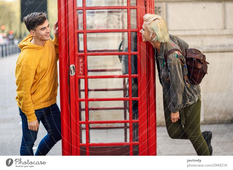 Young couple of friends near a classic British red phone booth Woman Human being Vacation & Travel Youth (Young adults) Man Old Young woman Young man Red Joy