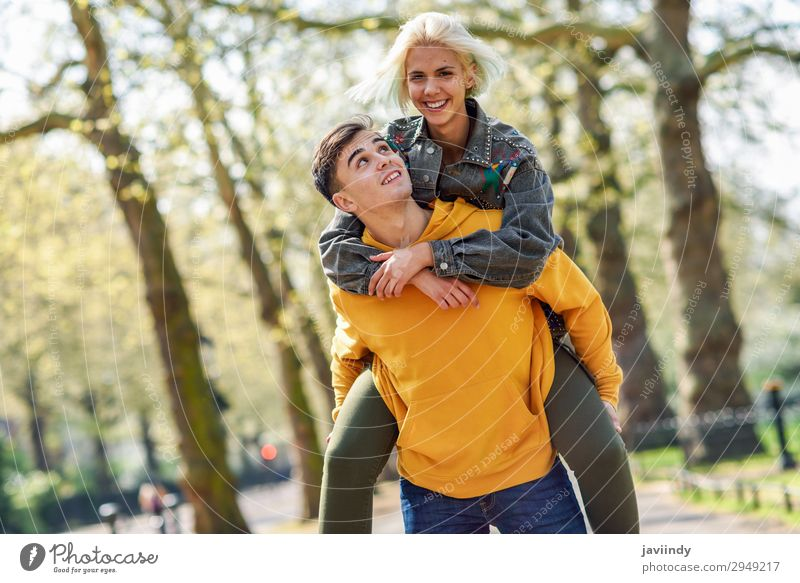 Boyfriend carrying his girlfriend on piggyback. Lifestyle Joy Happy Beautiful Leisure and hobbies Human being Masculine Feminine Young woman