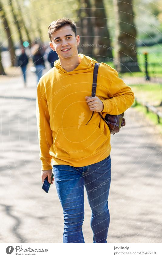 Young urban man walking in street in an urban park in London. Lifestyle Happy Vacation & Travel Telephone PDA Technology Human being Masculine Young man