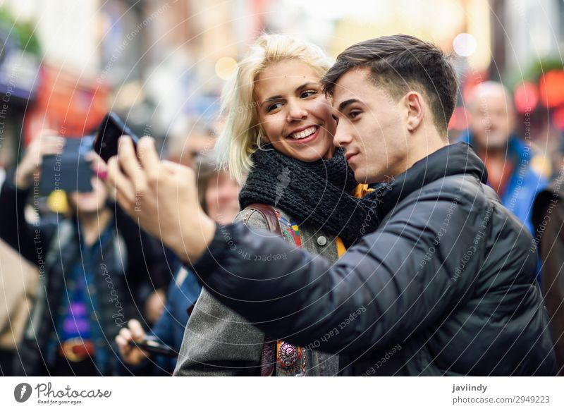 Happy couple of tourists taking selfie in a crowded street. Woman Human being Vacation & Travel Youth (Young adults) Man Young woman Town Beautiful Young man
