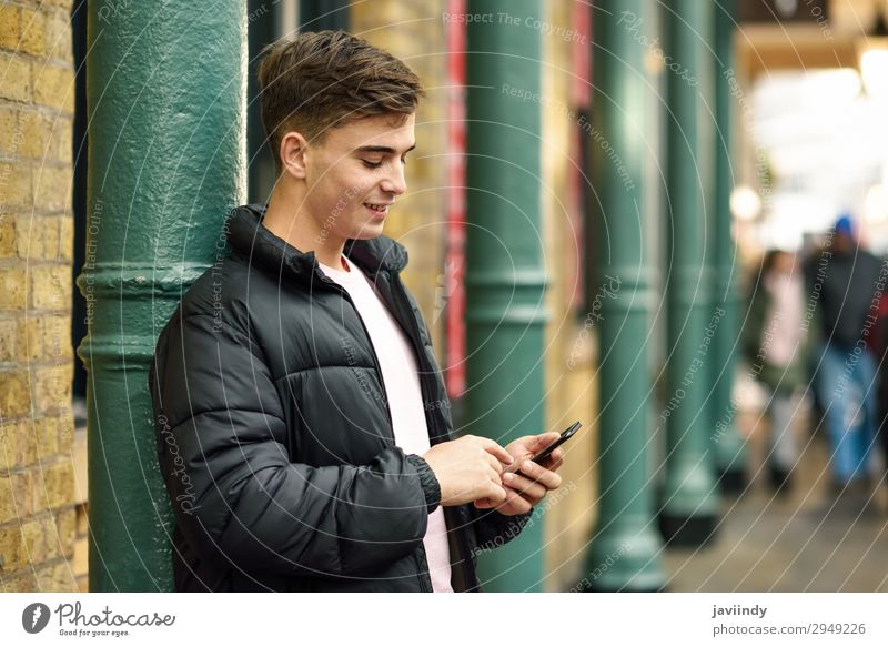 Young urban man using smartphone in urban background. Lifestyle Style Happy Telephone PDA Technology Human being Masculine Young man Youth (Young adults) Man