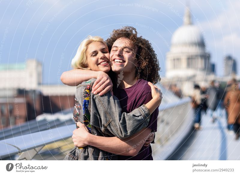 Happy couple hugging by Millennium bridge, River Thames, London. Woman Human being Youth (Young adults) Man Young woman Young man Joy 18 - 30 years Street