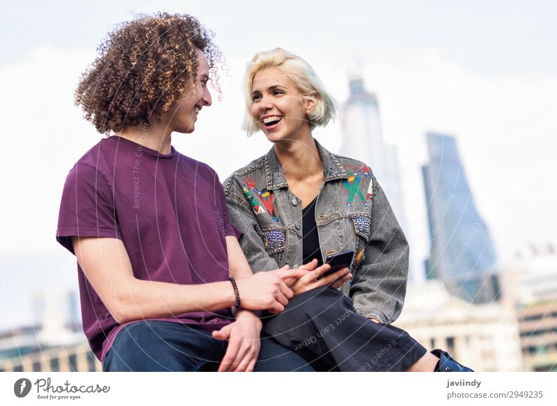 Happy couple talking sitting near River Thames. Lifestyle Joy Hair and hairstyles To talk Telephone PDA Technology Human being Masculine Feminine Young woman