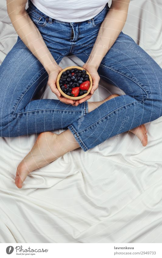 woman holding wooden bowl with organic berries Above Bed Bedclothes Bedroom Blueberry Bowl Denim Diet Faceless Woman Fresh Young woman Hand Healthy