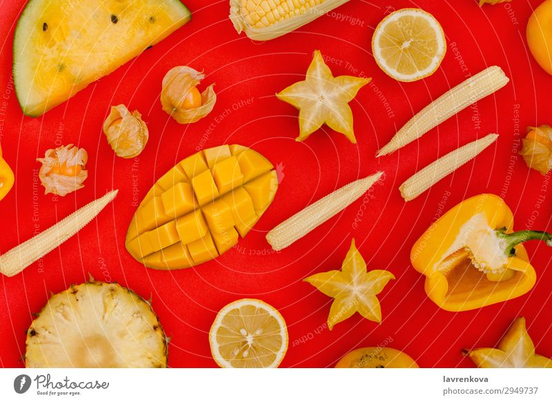 various yellow and orange fruits and vegetables on red bell Carambole Lemon Citrus fruits Corny Cut flat Fresh Healthy Healthy Eating lay Mango Organic Pepper