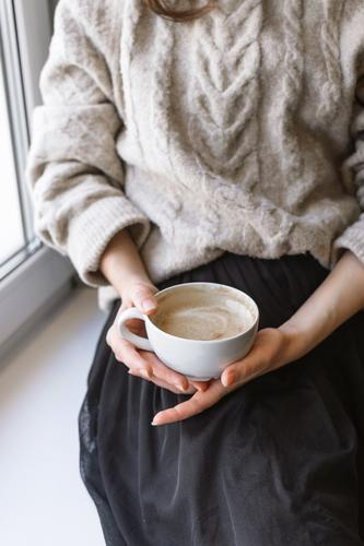 woman's holding cup with latte in front of the window Autumn Winter Relaxation Sweater Breakfast Interior shot Hand Cup Mug Warmth Cozy Café Close-up Coffee