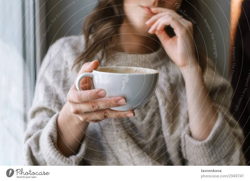 woman's holding cup with latte in front of the window selective focus Café Close-up Coffee Cup Beverage Drinking Woman Shallow depth of field Young woman Home