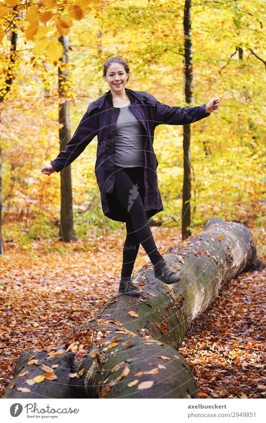 young woman balancing on tree trunk in autumn forest Lifestyle Joy Leisure and hobbies Human being Feminine Young woman Youth (Young adults) Woman Adults 1