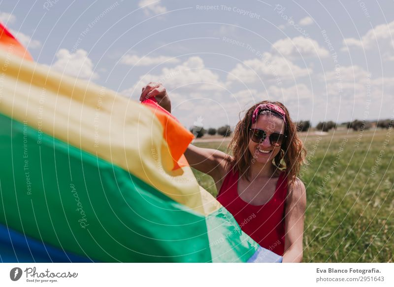 Woman holding the Gay Rainbow Flag on green meadow outdoor Human being Nature Youth (Young adults) Young woman Summer Blue Colour Green Landscape Red Sun Joy