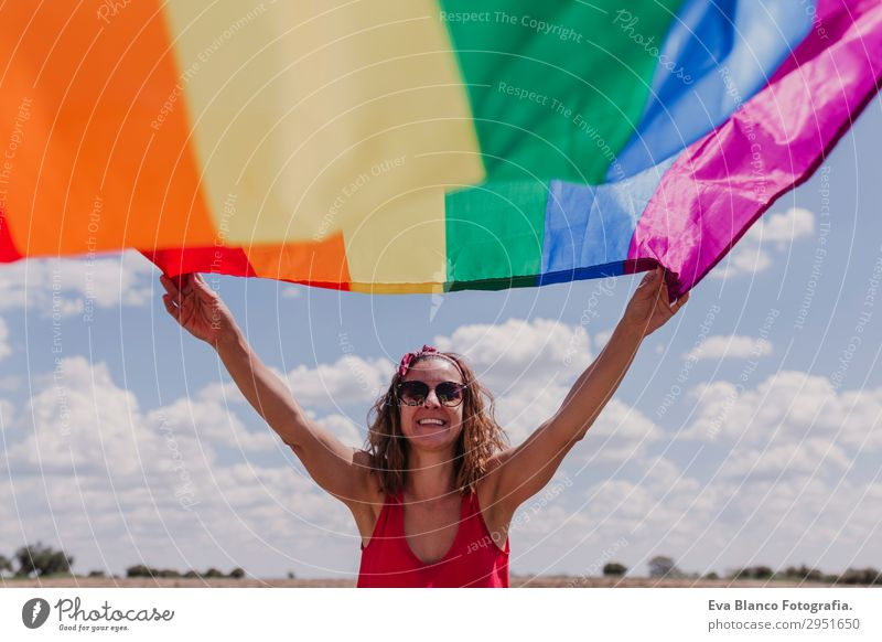 Woman holding the Gay Rainbow Flag over blue sky outdoors Human being Sky Nature Youth (Young adults) Young woman Summer Blue Colour Green Red Sun Clouds Joy