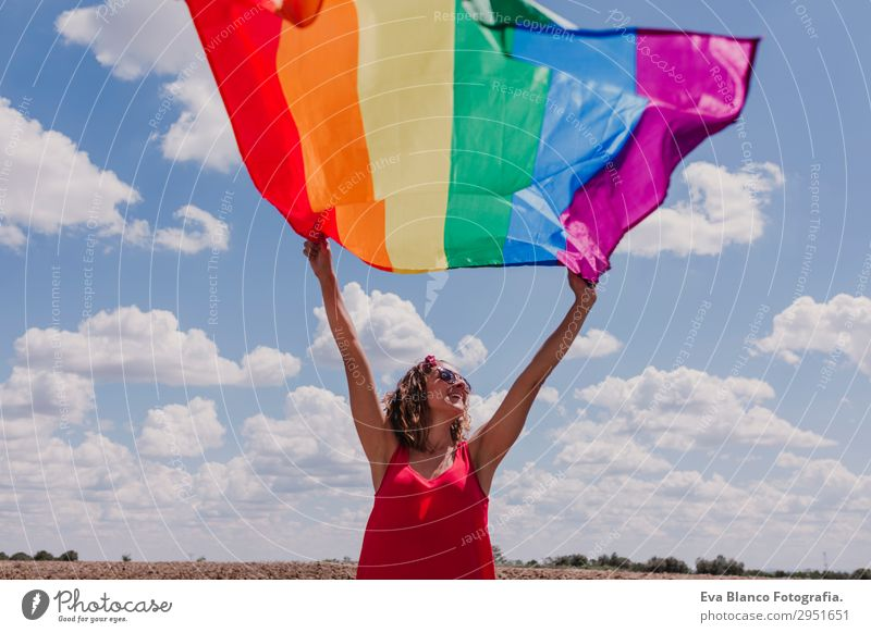 Woman holding the Gay Rainbow Flag over blue sky Human being Sky Nature Youth (Young adults) Young woman Summer Blue Colour Green Red Sun Clouds Joy