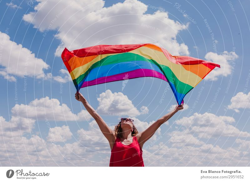 Woman holding the Gay Rainbow Flag over blue sky Human being Sky Nature Youth (Young adults) Young woman Summer Blue Colour Green Red Sun Clouds Joy Lifestyle