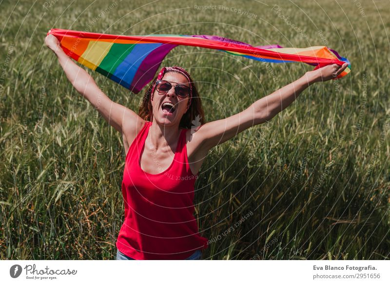 Woman holding the Gay Rainbow Flag on a green meadow outdoors Human being Nature Youth (Young adults) Young woman Summer Plant Blue Colour Green Red Sun Joy
