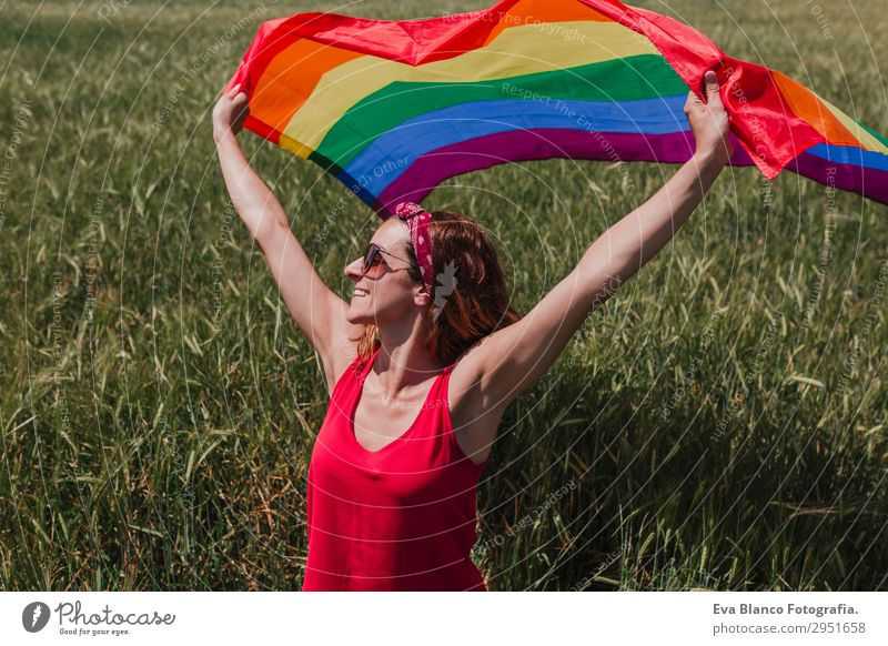 Woman holding the Gay Rainbow Flag on green meadow outdoor Human being Nature Youth (Young adults) Young woman Summer Plant Blue Colour Green Red Sun Joy