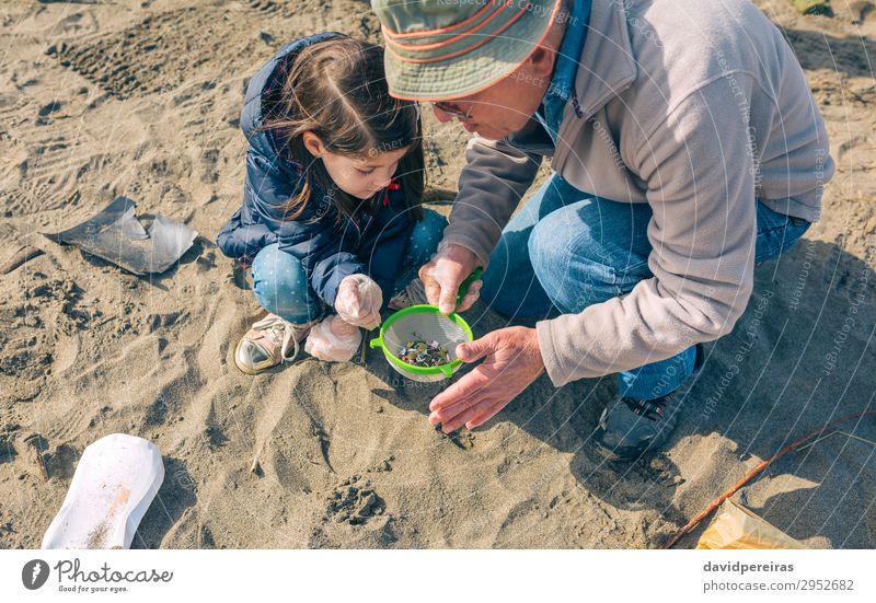 Volunteers cleaning the beach Beach Child Work and employment Human being Woman Adults Man Grandfather Family & Relations Environment Sand Hat Sieve Plastic Old