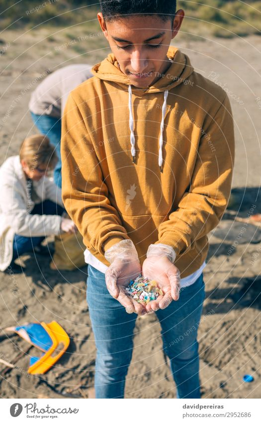 Young man showing microplastics Human being Man Old Hand Beach Adults Environment Group Sand Dangerous Plastic Indicate Trash Teamwork Vertical