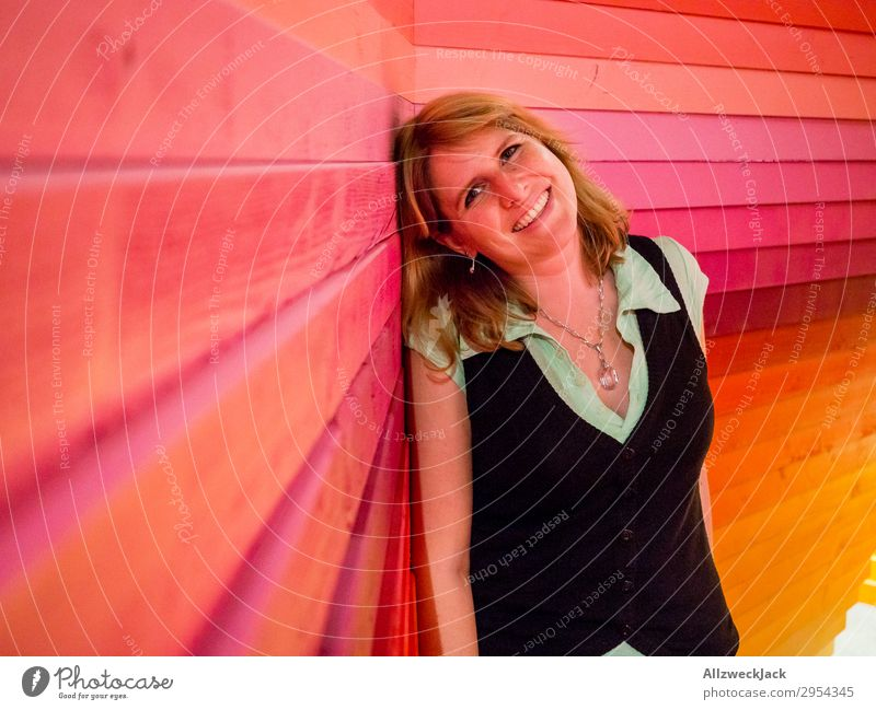 young woman leans happily against a colourful wooden wall Interior shot 1 Person Young woman Artificial light Portrait photograph Forward