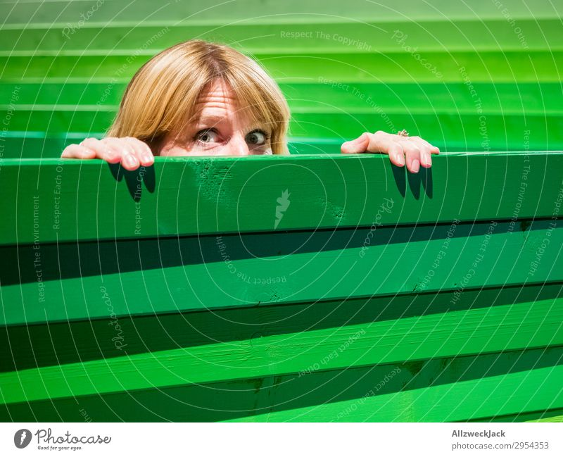 Young woman looks carefully over a wooden fence Head Fence Wooden fence Border Spy Looking Observe Caution Green Timidity Hesitate look out look over Hide