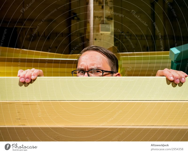 Young man looks curiously over a barrier Interior shot 1 Person Artificial light Portrait photograph Forward Looking into the camera Eyeglasses Fence Barrier